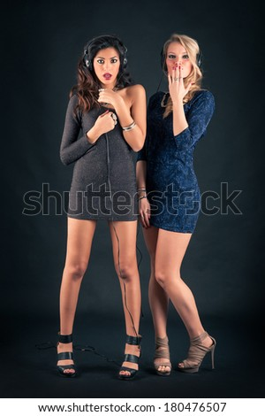 Blonde and brunette women portrait while listening to music with headphones on dark background.