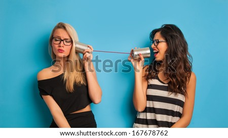 Blonde and brunette women talking with tin can telephone against blue background.
