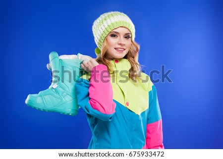 blonde attractive young caucasian girl in colorful ski suit and wool hat hold blue ski boots with one hand, look at camera