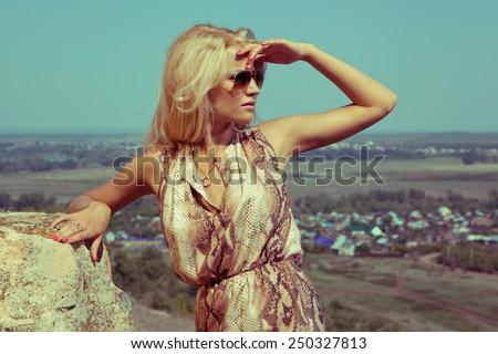 Blonde beautiful woman dress on the rocks. Summer day. Hot weather. Landscape. Fashion industry. Fashion style. Horizon.