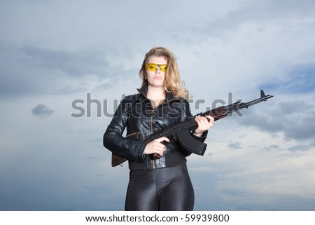 Blonde beautiful woman on the roof in yellow glasses holding weapon