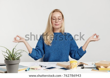 Blonde beautiful young female has relaxation after long tiredsome work with papers and books, meditates at working place, tries to concentrate, has minute rest, isolated over white background. ストックフォト ©