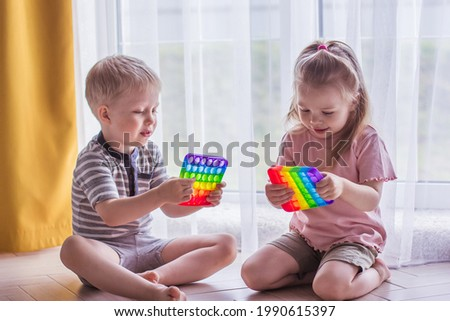 Blonde boy and girl children sit on the floor near the window and play silicone toy antistress pop it. Pop it sensory toy. Stress relief. Colorful anti stress silicone sensors toy