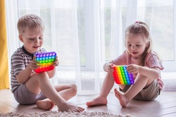 Blonde boy and girl Kids play with pop it sensory toy. Trendy silicon fidgeting game for stressed children and adults. Squishy soft bubble toys. Kid playing with rainbow color pop-it