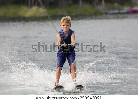 Blonde Boy learning to waterski on a lake #250543051