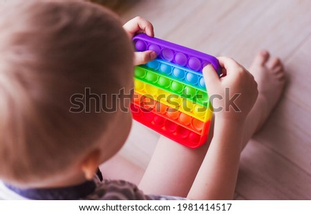 Blonde boy playing with rainbow pop it fidget toy. Push bubble fidget sensory toy - washable and reusable stress relief toy. Antistress toy for child with special needs. Mental health concept