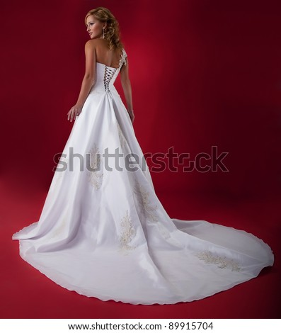 Blonde bride fashion model in long white wedding dress on red background