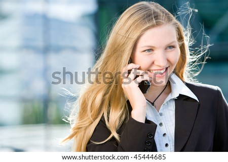 Blonde business woman in front of office building talking on cell mobile phone