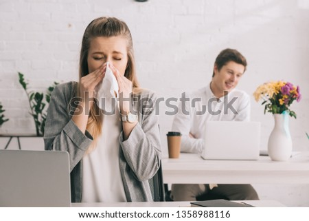 blonde businesswoman sneezing in tissue with closed eyes near coworker in office  #1358988116