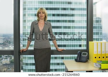 Blonde businesswoman standing beside office window, smiling, front view, portrait