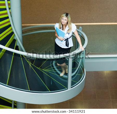 Blonde businesswoman walking up stairs in office