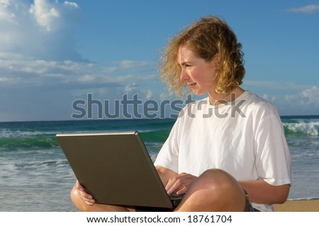 Blonde businesswoman with notebook on beach - sunrise light. Shot in Sodwana Bay Nature Reserve, KwaZulu-Natal province, Southern Mozambique area, South Africa.