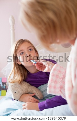 Blonde caucasian mother wearing bathrobe, takes teen-aged daughter's temperature while on her bed, looking at each other.