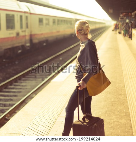 Blonde caucasian woman waiting at the railway station with a suitcase. #199214024