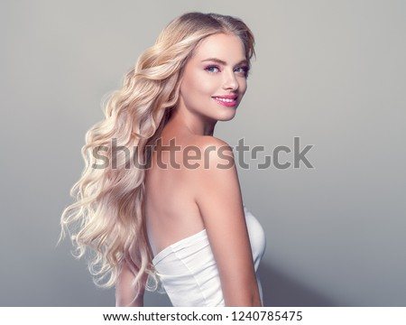 Blonde curly long hair woman with beauty makeup over gray background
