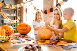 Blonde cute family of mother and two siblings making a jackolantern, boy is taking off the tail of pumpkin, yellow candles, treats, fall leaves and spiders on the table, garlands on windows