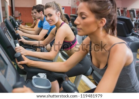 Blonde enjoying exercising on exercise bike in gym with other people