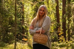 Blonde European girl in a beautiful forest holding a basket, with crossed arms, smiling, gray sweater, black jeans, forest trail, trees, green forest in Rubene. Rubene, Latvia.
