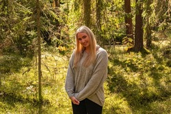 Blonde European girl in a beautiful forest smiling in a gray sweater, forest trail, trees, green forest in Rubene. Rubene, Latvia.