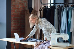 Blonde fashion designer excitedly look at laptop while working with sketches. Clothes, sewing machine on table. Background brickwall and rack of clothes