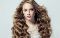 Blonde fashion  girl with long  and   shiny curly hair .  Beautiful  model  in light blue dress with wavy hairstyle .