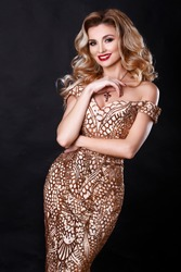 Blonde fashion woman with long curly hair and bright makeup wear luxury gold dress studio portrait. Gorgeous beauty model with jewelry. Fashionable sexy lady in elegant dress