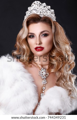 Stock Photo Blonde fashion woman with long curly hair and bright makeup wear luxury white fur and diamond tiara - beauty contest winner studio portrait. Gorgeous beauty model with jewelry.