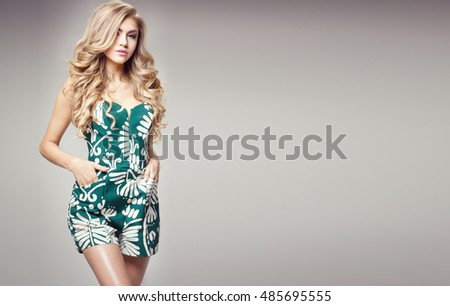 Blonde fashionable woman posing in studio. Girl with long curly hair and glamour makeup. Fashion photo.