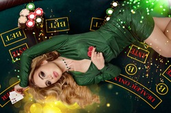 Blonde female in green dress is showing red chips and aces. Lying on playing table with colorful sparkles above her. Poker, casino. Close-up, top view
