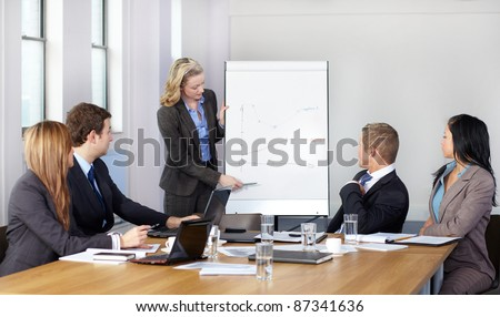 Blonde female present graph on flipchart during business meeting, while 4 more colleagues sits at conference table. Foto stock ©