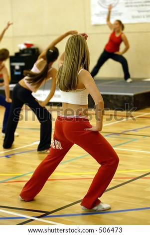 blonde female stretching in an aerobics exercise class with instructor in background