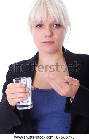 Blonde female takes some pills, holds glass of water, isolated on white