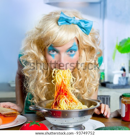 Blonde funny girl on kitchen eating pasta like crazy with blue makeup