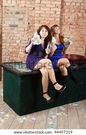 Blonde girl and brunette girl in a casino with big winning