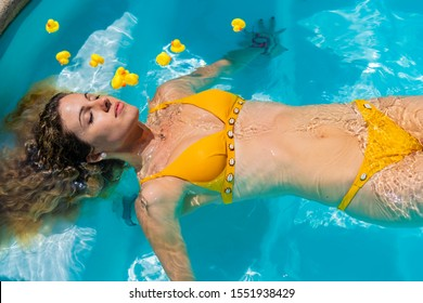 Stock photo of a blonde girl in bikini floating relaxed above the water of a pool surrounded by yellow rubber ducks. Holidays and relax