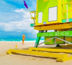 Blonde girl by a lifeguard tower in Miami Beach, USA