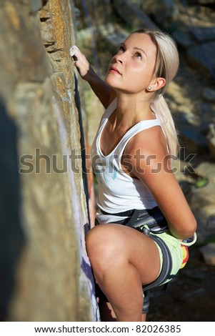 Blonde girl climbing on the rock on background