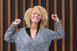 blonde girl hairstyle afro curls fun posing over wall background. Haircut scatters in motion. Fun mood ensured.