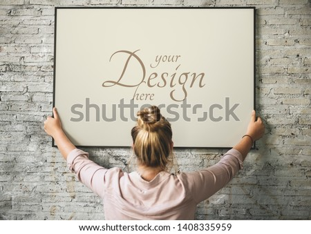Blonde girl hanging a frame mockup