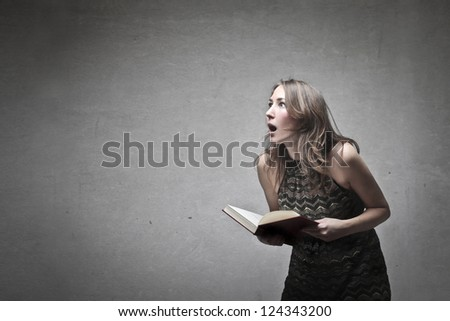 Blonde girl holding a book and screaming