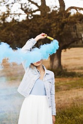 Blonde girl holding petard in her hand. Face is hidden by colored smoke. Outdoors