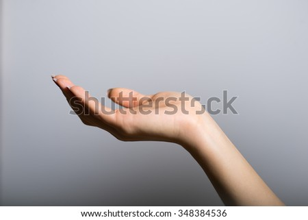 blonde girl holding something invisible in his hands, with clean skin, lifestyle concept studio photo isolated on a gray background