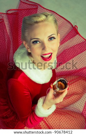 blonde girl in a red dress drinking champagne