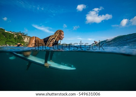 dccb6bc140 Blonde girl in black bikini - Surfer with white surfboard ready to dive  under big ocean