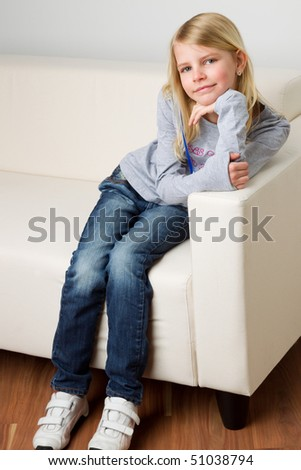 Blonde girl in jeans and sweatshirt is sitting on a sofa