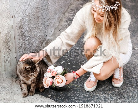 Blonde girl in light pastel clothes, a wreath of beads and a bouquet of roses stroking fluffy cat on the background of urban street. Friendly animal concept, pets protection