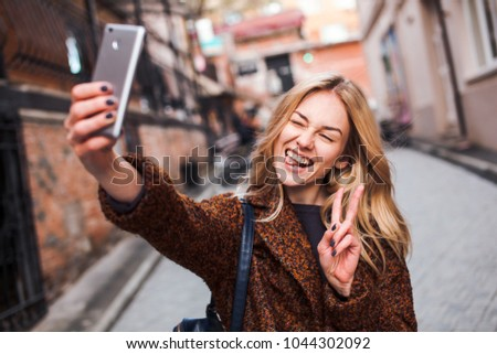 Blonde girl in terracotta coat wearing casual outfit making selfie portrait with her phone outdoors having fun and fooling