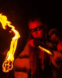 Blonde girl in the image of a Viking in animal skin, with a knife and a burning torch in a dark cave.