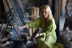 Blonde girl in vintage viking clothing prepares food in a cauldron on a fire