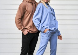 Blonde girl is standing in blue sport outfit. Man wears brown hoodie and black pants. Couple is wearing street matching outfit
